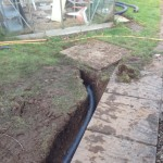 Trench with drain pipe ending in water drain well